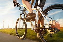 Low section of mature man riding electric bicycle with wind turbine at sunset, Bavaria, Germany