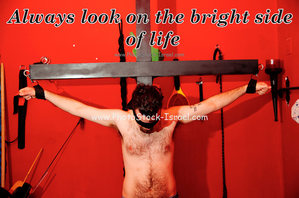 Famous quotes series: Always look on the bright side of life Crucified blindfolded young man in a BDSM dungeon