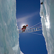 Ngawang Sherpa crosses a massive crevasse on a ladder; at 18,000 feet in the Khumbu Icefall, Everest, Nepal.
