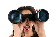 Woman looks through a binoculars facing camera wide angle view