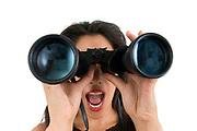 Woman looks through a binoculars facing camera wide angle view