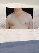 A bed with a photograph of bare breasted man under the blankets.