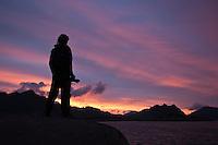 Silhouette of person holding camera watches scenic sunset, Lofoten islands, Norway