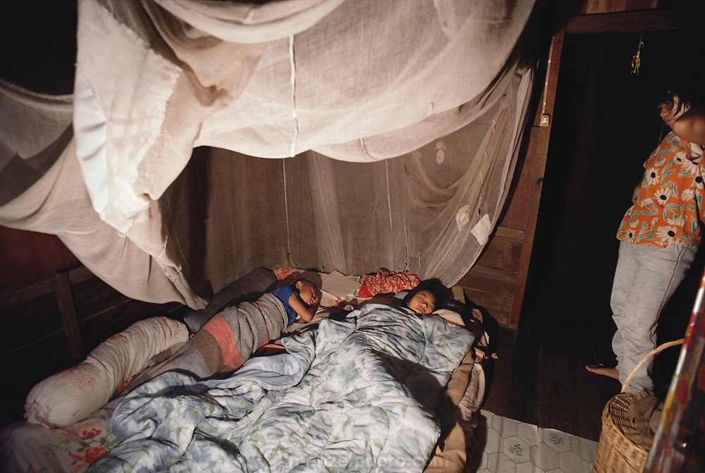 On a school morning before first light, Buaphet wakes her son and daughter who are sleeping in the second bedroom of their house on stilts, which is located at the edge of a rice field. Thailand. The Khuenkaew family lives in a wooden 728-square-foot house on stilts, surrounded by rice fields in the Ban Muang Wa village, outside the northern town of Chiang Mai, in Thailand. Material World Project.