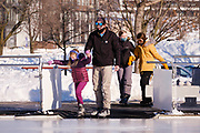 03 JANUARY 2021 - DES MOINES, IOWA: A family walks onto the ice to skate on the last day the rink was open at Brenton Skating Plaza in downtown Des Moines. The ice skating rink usually opens in late November and stays open through late February or March, depending on weather. Covid restrictions limited capacity to less than half, skaters were encouraged to social distance, and skaters were required to wear proper face masks. This year the rink was forced to close January 3, after only six weeks, because it wasn't possible to comply with COVID-19 restrictions and still be profitable. Restrictions caused by the Coronavirus pandemic have limited many public events this winter in Iowa.    PHOTO BY JACK KURTZ