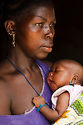 A woman holds her child in the village of Mongunde, Sierra Leone on Wednesday April 21, 2010.