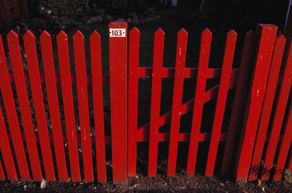 Red picket fence in front of weekend cottages. Copenhagen, Denmark.