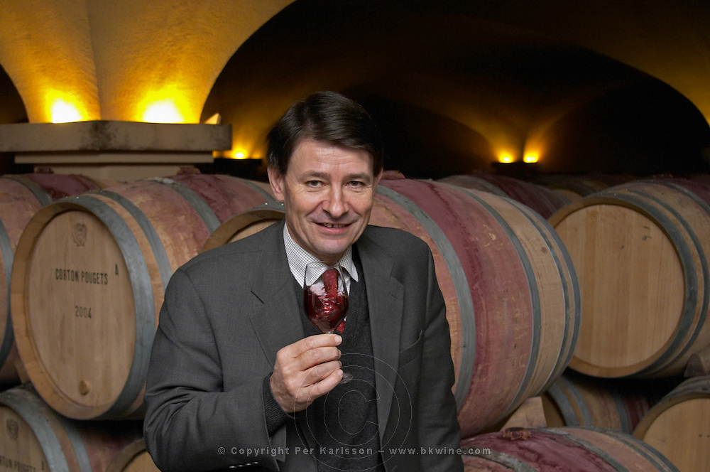 The old style vaulted barrel aging cellar with barriques pieces with maturing wine. General Manager Pierre-Henri (Henry) Gagey posing in front of barrels with a glass of wine., Maison Louis Jadot, Beaune Côte Cote d Or Bourgogne Burgundy Burgundian France French Europe European
