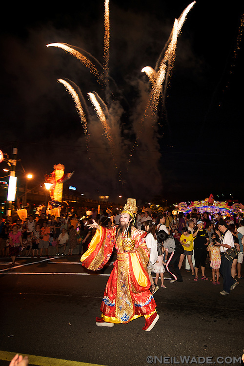 A marcher in the 2011 Keelung Ghost Festival Parade throws gifts to the crowd.
