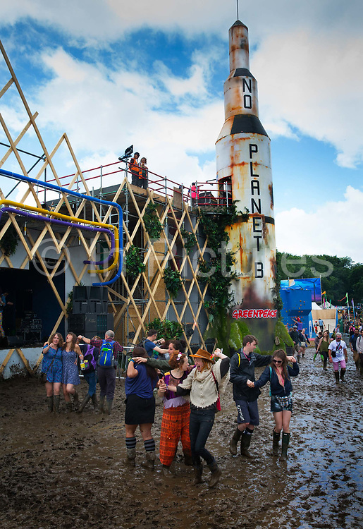 People dancing in the mud in front of a rocket ship in the Greenpeace field. The Glastonbury Festival is the largest greenfield festival in the world, and is now attended by around 175,000 people. Its a five-day music festival that takes place near Pilton, Somerset, United Kingdom. In addition to contemporary music, the festival hosts dance, comedy, theatre, circus, cabaret, and other arts. Held at Worthy Farm in Pilton, leading pop and rock artists have headlined, alongside thousands of others appearing on smaller stages and performance areas.