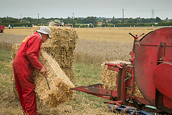 A farm worker stacking bales produced by a vintage baling machine at the Essex Country Show, Barleylands, Essex.