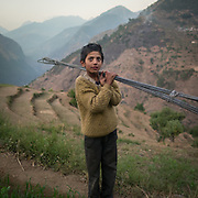 A kid carrying construction material, as part of mountain community work. In the Himalaya.