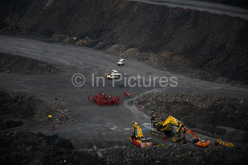 Hundreds of environmental activists stopping the open cast coal mine Ffos-y-Fran near Merthyr Tydfil, Wales from operating May 3rd 2016. Deep in the mine watched by engineers but otherwise unchallenged the activists congregrate. The activists from Reclaim the Power wants the mine shut down and a moratorium on all future open coal mining in Wales. The group Reclaim the Power had set up camp near by and had over three days prepared the action and up to 300 activists all dressed in red went into the mine in the early morning. The activist were plit in three groups and carried various props signifying the red line in the sand, initially drawn in Paris at the COP21. The mine is one of the largest open cast coal mines in the UK and is run by Miller Argent who have to date extracted 5million tons of coal. The activists entered the mine unchallenged by any security or police and the protest went on peacefully till mid afternoon with no arrests made.  Open coal mining is hugely damaging to the local environment and  contributing to global climate change.