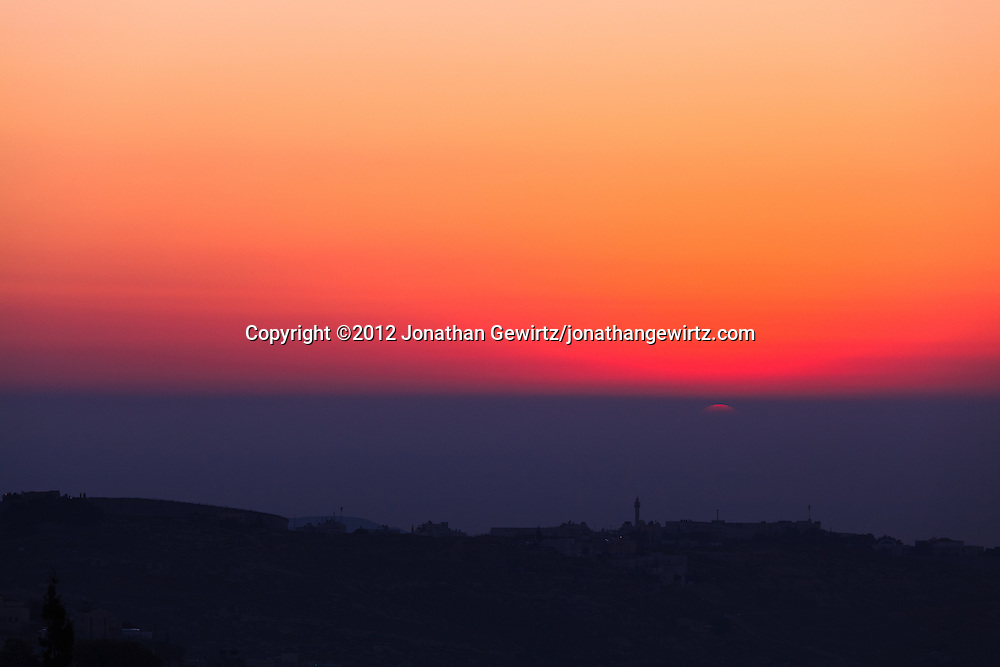 The rising sun emerges from haze behind the village of Abu Dis on the eastern outskirts of Jerusalem. WATERMARKS WILL NOT APPEAR ON PRINTS OR LICENSED IMAGES.
