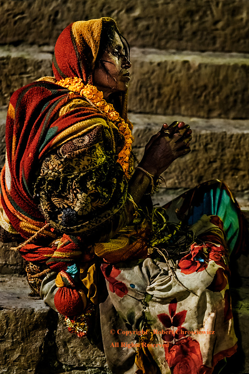 Evening Prayers: A dirty and disheveled woman prays on the steps of the Assi Ghat, Varanasi India.