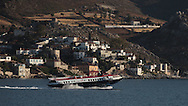 A ferryboat scims by the island of Hydra, Greece. Photograph by Dennis Brack