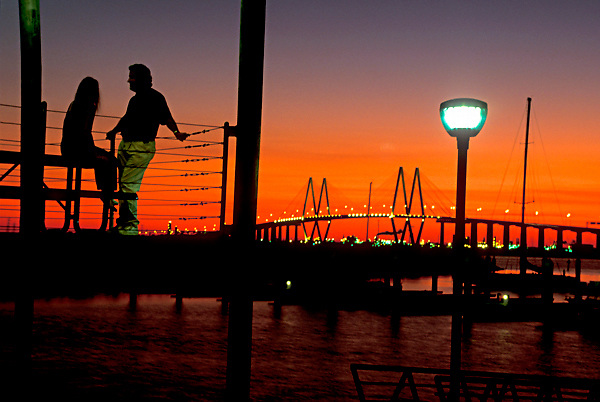 Man and woman on a pier in Galveston Texas at sunset