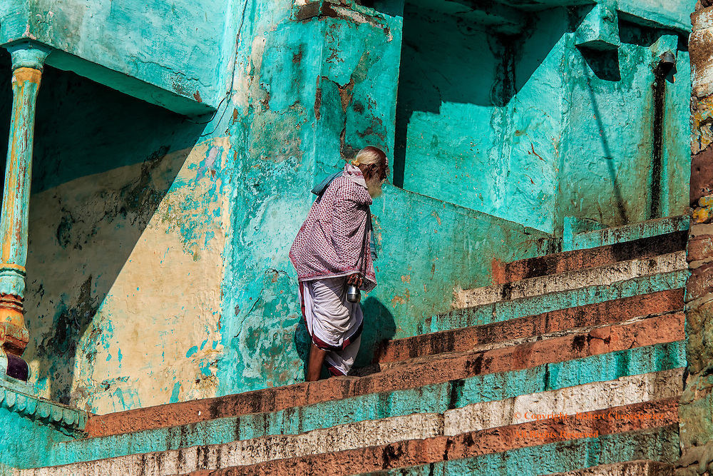 Stairs of Varanasi: An elderly man slowly makes his way up the steep, numerous, multicoloured (white, red and teal) stairs from the Ganges River, Varanasi India.