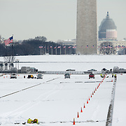 Snow covers the National Mall as workers continue work on the drained and snow-covered Reflecting Pool.