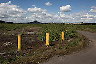 'Untitled, 2014' from the project 'The Fall and Rise of Ravenscraig' by photographer Colin McPherson.<br /> <br /> The photograph shows three traffic bollards on the site of the former steelworks at Ravenscraig.<br /> <br /> This project, photographed in 2014, looks at the topography of the post-industrial landscape at Ravenscraig, the site until its closure in 1992 of the largest hot strip steel mill in western Europe. In its current state, Ravenscraig is one of the largest derelict sites in Europe measuring over 1,125 acres (4.55 km2) in size, an area equivalent to 700 football pitches or twice the size of Monaco. It is currently being developed with a mix of housing, retail and the home of South Lanarkshire College and the Ravenscraig Regional Sports Facility.