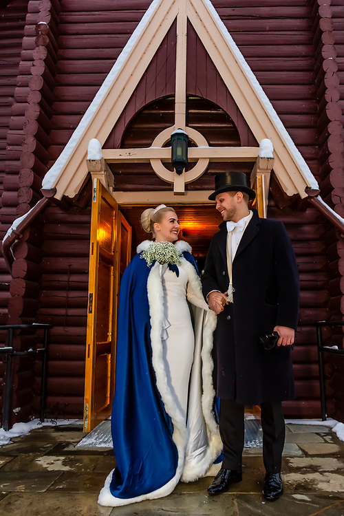 Bride and groom outside the church after their wedding ceremony at Plassen Church (kirke), a wooden (stave) church originally built in 1879. It burnt to the ground in 1904 and was rebuilt in 1907. Trysil, Norway.