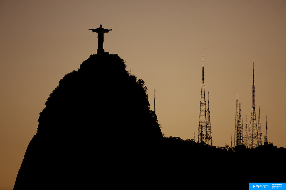 The iconic Cristo Redentor, Christ the Redeemer statue at sunset with communication antenna atop the mountain Corcovado shot from Suger Loaf Mountain. The Christ statue was voted one of the seven wonders of the modern world in 2007. It was designed by Brazilian Heitor de Silva Costa and was inaugurated in 1931 having taken years to assemble. Rio de Janeiro, Brazil. 21st July 2010. Photo Tim Clayton..