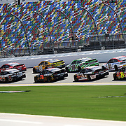 The pack drives down the front stretch during the 57th Annual NASCAR Coke Zero 400 race first practice session at Daytona International Speedway on Friday, July 3, 2015 in Daytona Beach, Florida.  (AP Photo/Alex Menendez)