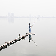 A fisherman stands on a narrow wooden jetty to cast his line on West Lake (Ho Tay) in Hanoi, Vietnam, using a rod combined with a separate hand line rather than a fixed reel. The thick haze obscures the far shore. Like most of the lakes in Hanoi, West Lake is heavily polluted, which makes the fish caught there of questionable quality for eating.