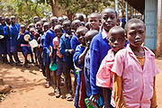 Pupils wait for their lunch to be served at Graissa Road Primary School in Thika, Kenya. The kitchen staff wages are paid by AFCIC (Action for children in conflict). The majority of the 800 pupils are from the Kiandutu slum and rely heavily on this meal.