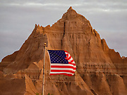 American flag at sunrise in Badlands Campground in Badlands National Park, South Dakota, USA. The intricately carved cliff of the Badlands Wall constantly retreats as it erodes and washes into the White River Valley below.