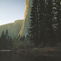 Massive El Capitan reflects in the Merced River in Yosemite Valley.