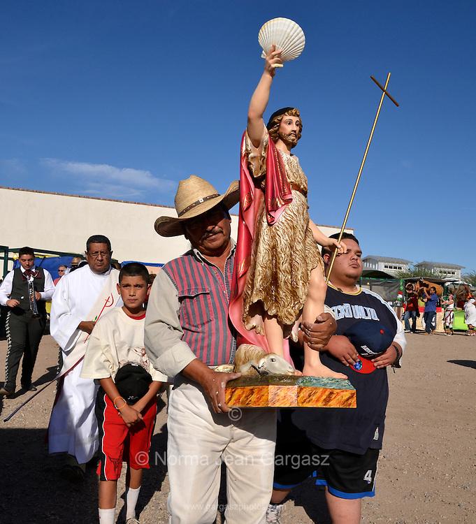 Celebrants honor Saint John the Baptist, as one who brings seasonal monsoon rain to the desert, at the 16th annual El Dia De San Juan Fiesta at Mercado San Augustin on Monday, June 24, 2013, in Tucson, Arizona, USA.