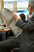 elderly Asian businessman reading the economic section of a news paper in a coffee bar