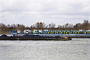 Nederland, Nijmegen, 20-2-2020  Binnenvaartschip, duwcombinatie, beladen met kolenvaren over de Waal richting Duitsland. De lading komt uit de haven van Rotterdam en is op weg naar het Ruhrgebied als brandstof voor hoogovens en elektriciteitscentrales ... Hij kruist een schip wat richting Rotterdam vaart beladen met vrachtwagens en tractoren .FOTO: FLIP FRANSSEN