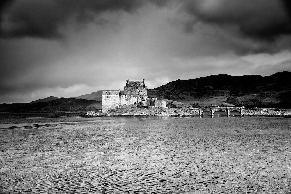 Eilean Donan offers one of the most iconic images of Scotland. It is situated on an island at the point where three great sea lochs meet, and surrounded by some majestic scenery.<br /> <br /> First inhabited around the 6th century, the first fortified castle was built in the mid 13th century and stood guard over the lands of Kintail. Since then, at least four different versions of the castle have been built and re-built as the feudal history of Scotland unfolded through the centuries.<br /> <br /> Partially destroyed in a Jacobite uprising in 1719, Eilean Donan lay in ruins for the best part of 200 years until Lieutenant Colonel John MacRae-Gilstrap bought the island in 1911 and proceeded to restore the castle to its former glory. After 20 years of toil and labour the castle was re-opened in 1932.<br /> <br /> This photograph is a monochromatic version of the view of Eilean Donan Castle from the south, on Loch Duich through to Loch Alsh. The photograph can be purchased as print, mounted print in frames, canvas or aluminum or as a digital file.