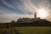 A woman walking towards Neist Point Lighthouse in Glendale on the 4th September 2016 on the Isle of Skye in Scotland in the United Kingdom. Neist Point is the most Westerly point on the Isle of Skye with views over Moonen Bay to Waterstein Head.