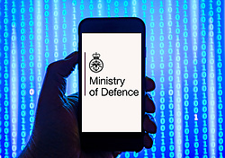 Person holding smart phone with Ministry of Defence  logo displayed on the screen. EDITORIAL USE ONLY