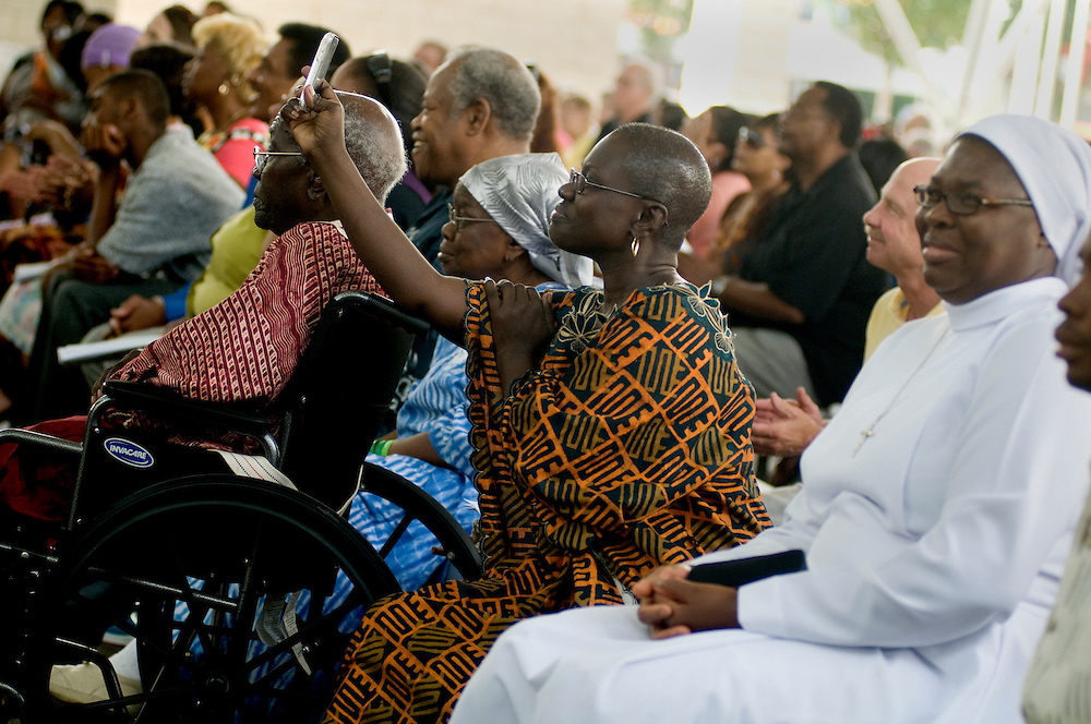 A woman records part of the ceremony on her phone, Sunday, Aug. 1.