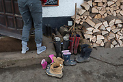 A woodland walker leaves his muddy boots next to a pile of other outdoor walkers' boots which have been left outside the Bucks Head pub in Godden Green, 5th January 2019, in Kent, England.