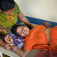 Ramvati Adivasi (left) tends to Mukhi, age 22 (in orange), pregnant with her third child (her previous two children died before reaching their first birthdays) at the Satanwarda Community Health centre. Adivasi had taken Mukhi for a consultation with the ANM. Adivasi is is an ASHA (local female health advisor). She provides a free referral service to local women, keeping them in touch with government health services. Adivasi receives a fee from the government for every referral. This is one means by which the government and partners UNICEF are increasing the rate of institutional deliveries in Madhya Pradesh state. Adivasi is a presenter on community radio station Dharkan 107.8 FM. Adivasi has recorded several programs informing women of government health services. ..Shivpuri district in Madhya Pradesh suffers from poor health outcomes. Of particular concern is the high rate of maternal mortality. One of the Indian government's aims, with partners Unicef, is to encourage the population to adopt practices to improve sanitation and health practices. In an area made up of traditionally disadvantage groups and suffering low literacy rates, this can be a challenge. ..A survey found that radio was the most readily accessible media by the Shivpuri community with more than half saying they tuned in several times a day. ..Dharkan 107.8 FM will go on air in July. The station that will broadcast to 75 villages in a 15-kilometer radius reaching 170,000 people...Rather than preaching educational messages, the station, which is already producing pilot programs, uses humor and folk artists performing in the local language to entertain and inform their audiences. There is a major impact, especially on women, who are contributing their voices to such wide-ranging issues as caste discrimination, female feticide and women,A?o?s empowerment. ..Photo: Tom Pietrasik.Shivpuri, Madhya Pradeh. India.June 2009