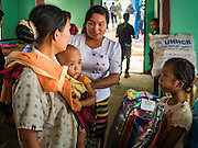 26 OCTOBER 2016 - MYAWADDY, KAYIN STATE, MYANMAR:  A family of Burmese refugees repatriated to Myanmar from Nupo Temporary Shelter refugee camp in Thailand walks into their new housing in a displaced persons facility for returning refugees in Myawaddy, Myanmar. Sixtyfive Burmese refugees living in the Nupo Temporary Shelter refugee camp in Tak Province of Thailand were voluntarily repatriated to Myanmar. About 11,000 people live in the camp. The repatriation was the first large scale repatriation of Myanmar refugees living in Thailand. Government officials on both sides of the Thai / Myanmar border said the repatriation was made possible by recent democratic reforms in Myanmar. There are approximately 150,000 Burmese refugees living in camps along the Thai / Myanmar border. The Thai government has expressed interest several times in the last two years in starting the process of repatriating the refugees.    PHOTO BY JACK KURTZ