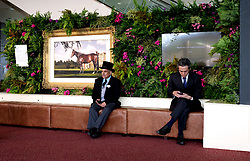 Two racegoers take a seat near a portrait of Estimate, a mare owned by Her Majesty Queen Elizabeth II and produced by artist Ripley during day two of Royal Ascot at Ascot Racecourse.
