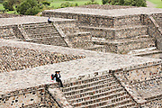People sit alone on the top of temples at the pre-columbian archeological site of Teotihuacan, Mexico state, Mexico.