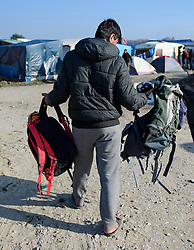 © Licensed to London News Pictures. 23/10/2016. Calais, France. Suitcases and rucksacks being handed out at the 'Jungle' camp in Calais ahead of it's demolition, which is scheduled for this week. French authorities have given an eviction order to thousands of refugees and migrants living at the makeshift living area of the French coast. Photo credit: Ben Cawthra/LNP