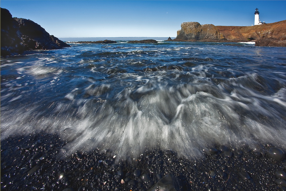 lighthouse view during a sunny day on the oregon coast. Rushing water moves ashore on a beach of round black pebbles.