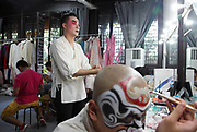 "Lead actor Zhang Jun applies makeup before performing in the Kun Ju opera ""Peony Pavilion"" in Shanghai, China, on 07 August, 2010. The modern adaptation of a traditional love story involves performance in a real Chinese garden together with soundtracks by renowned Chinese musician Tan Dun."