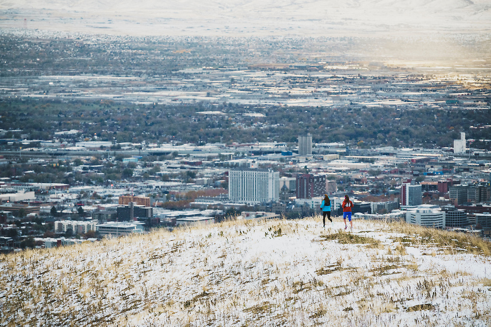 Mali Noyes and Annie MacWilliams running in the foothills above Salt Lake City, on a snowy day.
