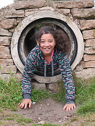 Girl coming out of playground tunnel