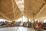"""Parent and teacher meeting under a bamboo canopy in the main theatre hall<br /><br />The Green School (Bali) is one of a kind in Indonesia. It is a private, kindergarten to secondary International school located along the Ayung River near Ubud, Bali, Indonesia. The school buildings are of ecologically-sustainable design made primarily of bamboo, also using local grass and mud walls. There are over 600 students coming from over 40 countries with a percentage of scholarships for local Indonesian students.<br /><br />The impressive three-domed """"Heart of School Building"""" is 60 metres long and uses 2500 bamboo poles. The school also utilizes renewable building materials for some of its other needs, and almost everything, even the desks, chairs, some of the clothes and football goal posts are made of bamboo.<br /><br />The educational focus is on ecological sustainability. Subjects taught include English, mathematics and science, including ecology, the environment and sustainability, as well as the creative arts, global perspectives and environmental management. This educational establishment is unlike other international schools in Indonesia. <br /><br />Renewable energy sources, including solar power and hydroelectric vortex, provide over 50% of the energy needs of the school. The school has an organic permaculture system and prepares students to become stewards of the environment. <br /><br />The school was founded by John and Cynthia Hardy in 2008."""