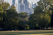 With the skyline of the capitals financial district, the City of London in the distance, man and his dogs walk in Ruskin Park, on 10th August 2018, in London, England.